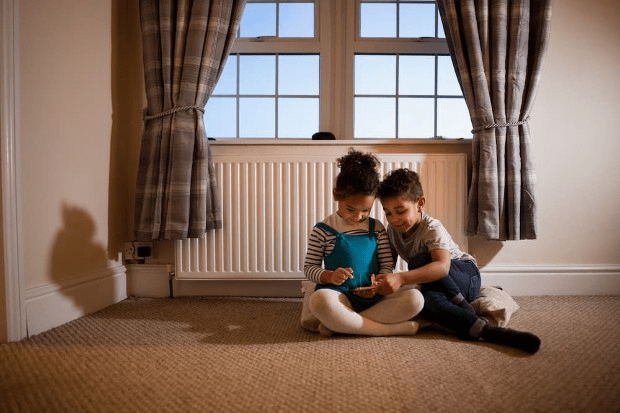Children playing in front of a radiator