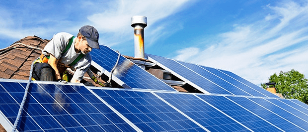 man fitting solar panels to roof